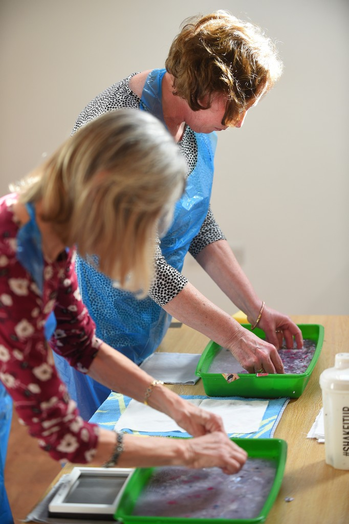 Two women, leaning over a table and with their hands in seed trays of water and paper pulp.