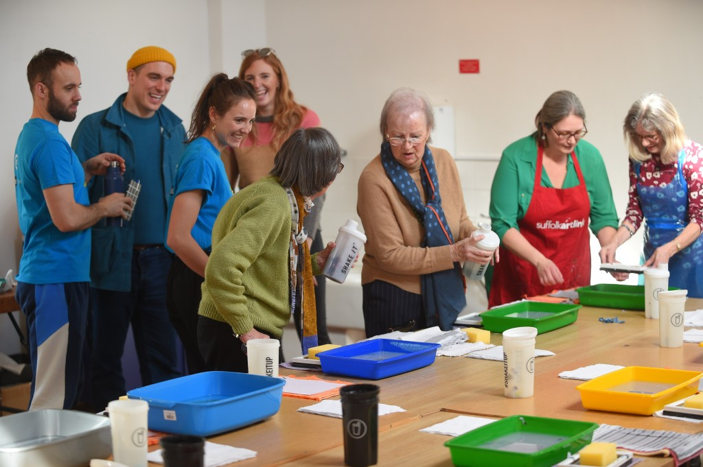 A group of people gathered round a large table, on which are trays of paper pulp and other equipment for making paper.