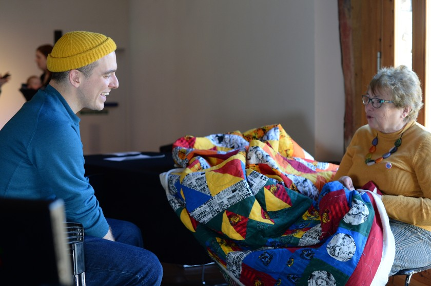 A woman sits stitching a large brightly coloured quilt as a man smiles and chats with her